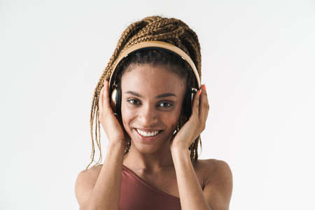 Portrait of beautiful smiling african brunette woman with dreadlocks a listening music via wireless headphones isolated on white background