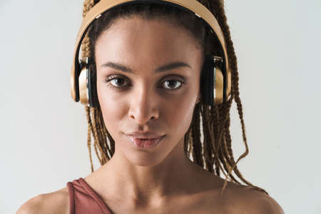 Close up portrait of beautiful smiling african brunette woman with dreadlocks a listening music via wireless headphones isolated on white background
