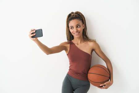 Image of a happy african sports woman with basketball taking a selfie by mobile phone while standing isolated over white wall background