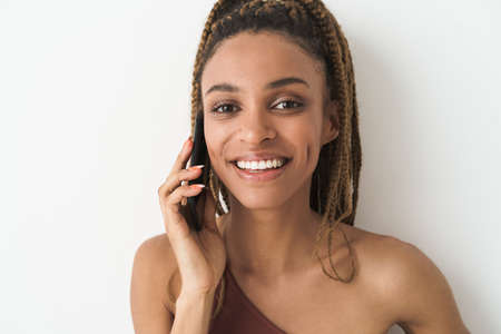 Young african american sportswoman with afro hair talking on mobile phone isolated over white background 版權商用圖片