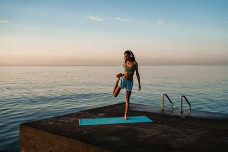 Image of focused african american girl in headphones doing yoga exercise on mat at concrete promenade