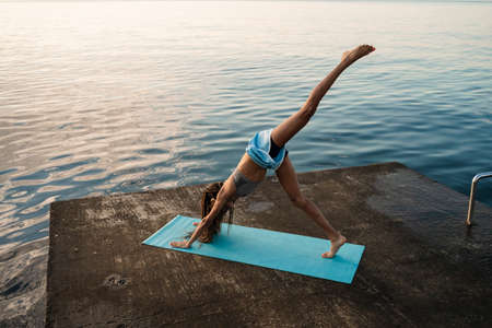 Image of focused african american girl in sportswear doing yoga exercise on mat at concrete promenade
