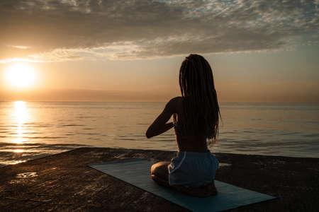 Image of calm african american girl in sportswear meditating on concrete promenade outdoors 版權商用圖片