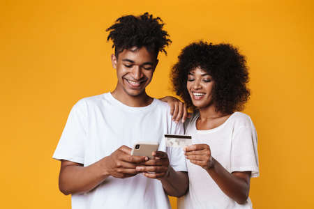 Image of smiling african american couple holding credit card and smartphone isolated over yellow wall