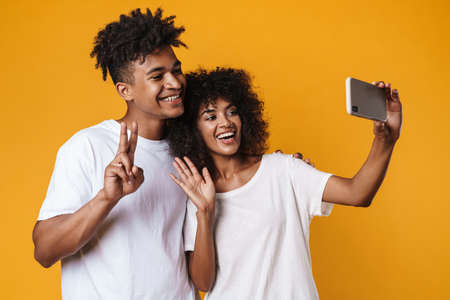 Image of african american couple gesturing peace sign while taking selfie on smartphone isolated over yellow wall