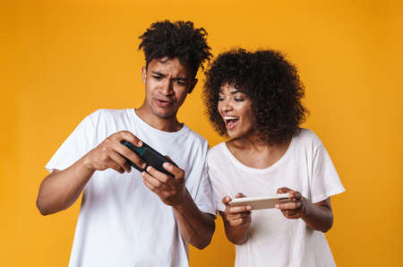 Photo of excited african american people playing online game on cellphones isolated over yellow background