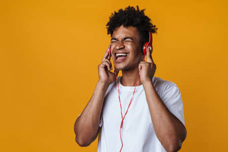 Image of excited african american guy listening music with headphones and singing isolated over yellow wall Zdjęcie Seryjne