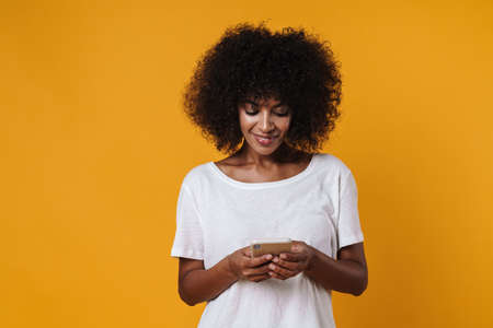 Image of happy african american girl smiling and using mobile phone isolated over yellow wall Zdjęcie Seryjne