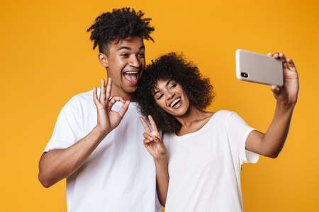 Image of african american couple gesturing peace sign while taking selfie on smartphones isolated over yellow wall Zdjęcie Seryjne