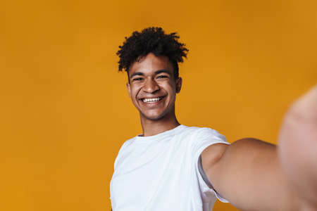 Image of happy african american guy smiling while taking selfie photo isolated over yellow wall