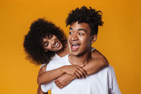 Image of funny african american couple laughing while piggyback riding isolated over yellow wall Zdjęcie Seryjne