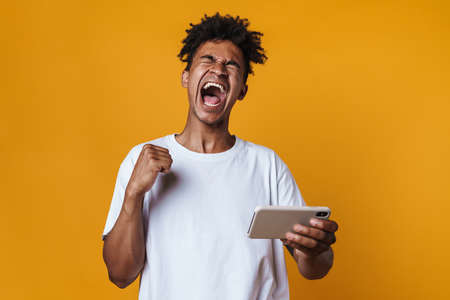 Image of african american guy making winner gesture and playing game on cellphone isolated over yellow wall