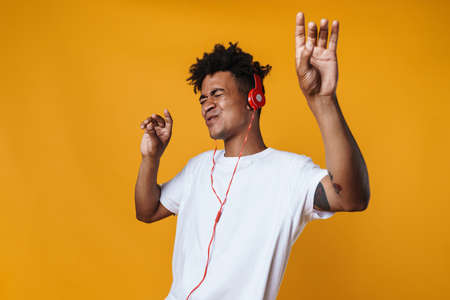 Image of excited african american guy listening music with headphones and dancing isolated over yellow wall Zdjęcie Seryjne