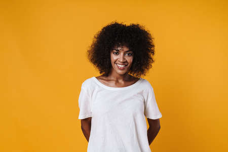 Image of happy african american girl smiling and looking at camera isolated over yellow wall