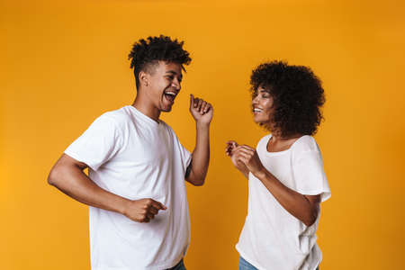 Image of cheerful african american couple dancing and singing isolated over yellow wall