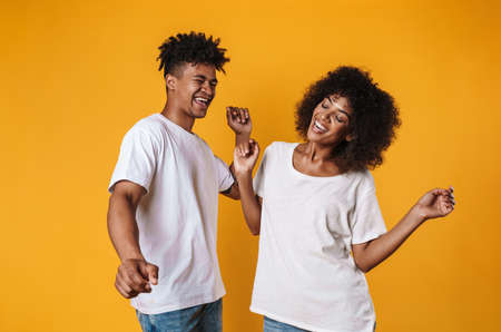 Photo of joyful african american people laughing and dancing isolated over yellow background