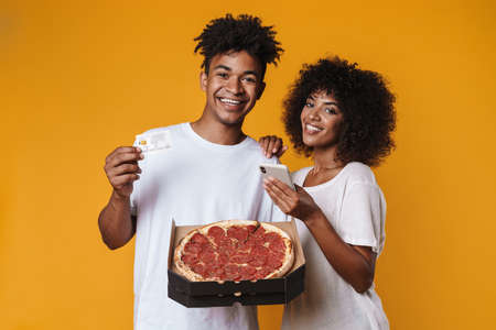 Image of delighted african american couple using credit card and cellphone while holding pizza isolated over yellow wall