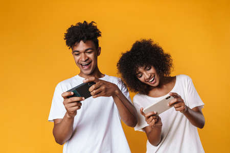 Image of cheerful african american couple playing online game on smartphones isolated over yellow wall