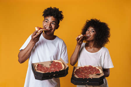 Image of delighted african american couple smiling and eating pizza isolated over yellow wall Zdjęcie Seryjne