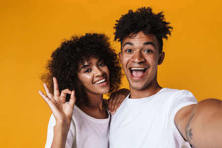 Image of african american couple gesturing ok sign while taking selfie photo isolated over yellow wall Zdjęcie Seryjne