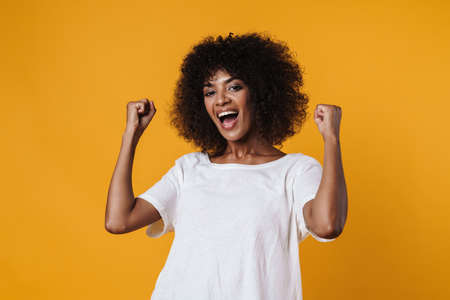 Image of excited african american girl making winner gesture isolated over yellow wall Zdjęcie Seryjne