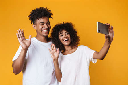 Image of african american couple waving hands while taking selfie on smartphone isolated over yellow wall Zdjęcie Seryjne