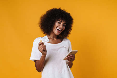 Image of joyful african american girl holding credit card and mobile phone isolated over yellow wall