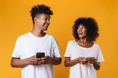 Photo of joyful african american people laughing and using cellphones isolated over yellow background Zdjęcie Seryjne