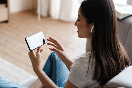 Image of smiling asian woman in earphones using mobile phone while sitting on sofa at home