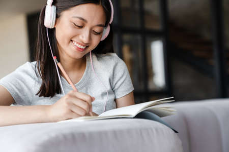 Image of smiling asian woman using headphones and writing down notes while sitting on sofa at home Zdjęcie Seryjne