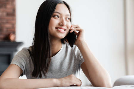 Image of happy asian woman smiling and talking on mobile phone while sitting on sofa at home