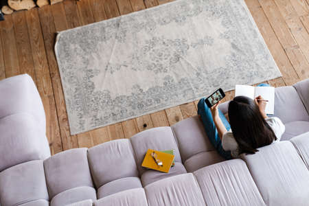 Image of young asian woman using mobile phone while writing down notes at home