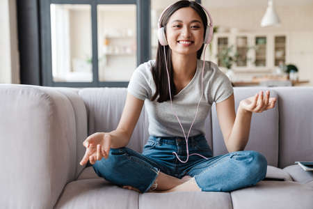 Image of happy asian woman smiling and listening music with headphones while sitting on sofa at home Zdjęcie Seryjne
