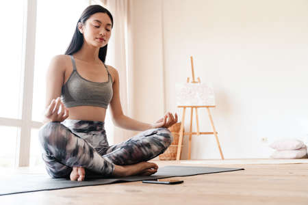 Image of focused asian girl in sportswear using mobile phone while meditating at home