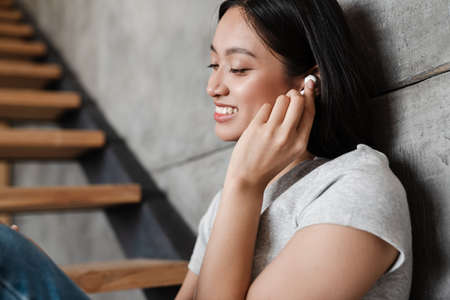 Image of smiling asian student girl using wireless earphones while sitting on stair at home