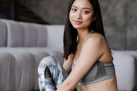 Image of beautiful asian girl in sportswear smiling and looking at camera while sitting at home Zdjęcie Seryjne