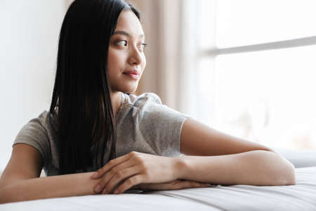 Image of pleased nice asian woman looking aside while sitting on sofa at home Zdjęcie Seryjne