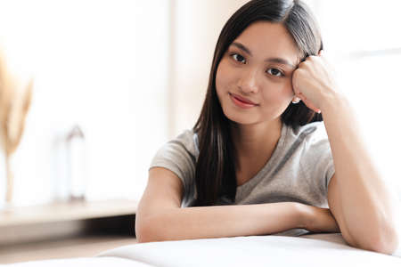 Image of happy asian woman smiling and looking at camera while sitting on sofa at home Zdjęcie Seryjne