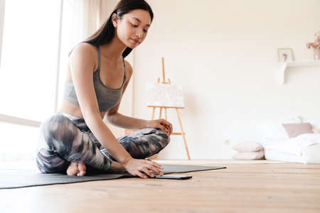Image of focused asian girl in sportswear using mobile phone while working out at home