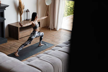 Image of concentrated asian woman in sportswear doing exercise while working out on mat at home