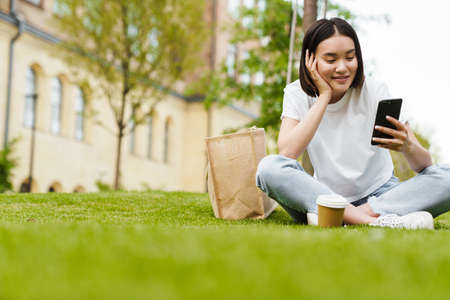 Photo of pleased young asian woman sitting outdoors on grass using mobile phone