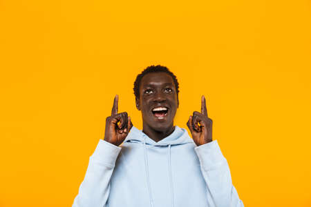 Image of happy african american guy in streetwear hoodie smiling and pointing fingers upward at copyspace isolated over yellow background