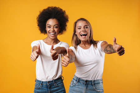 Image of a positive young multiracial girls friends posing isolated over yellow wall background while showing thumbs up gesture