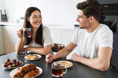 Image of a positive young loving couple at home having a breakfast