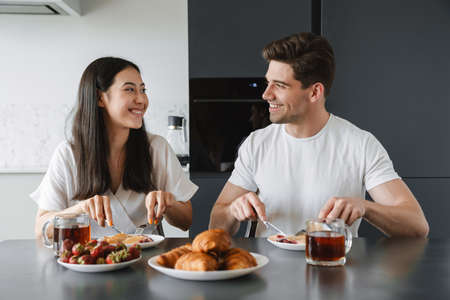 Photo of a cheerful young loving couple at home having a breakfast