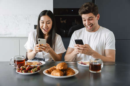 Portrait of a happy young couple using mobile phones while having tasty breakfast at the table in a kitchen Stockfoto