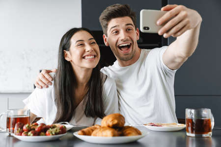 Young couple eating breakfast in the kitchen and taking selfie