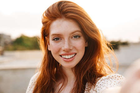 Image of cheerful ginger girl taking selfie and smiling at camera at city street