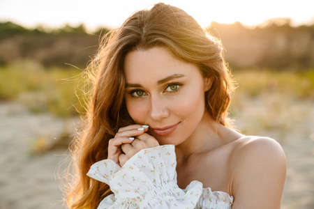 Young caucasian attractive brunette woman smiling and looking at camera outdoors