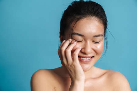 Image of shirtless asian girl posing and laughing at camera isolated over blue background